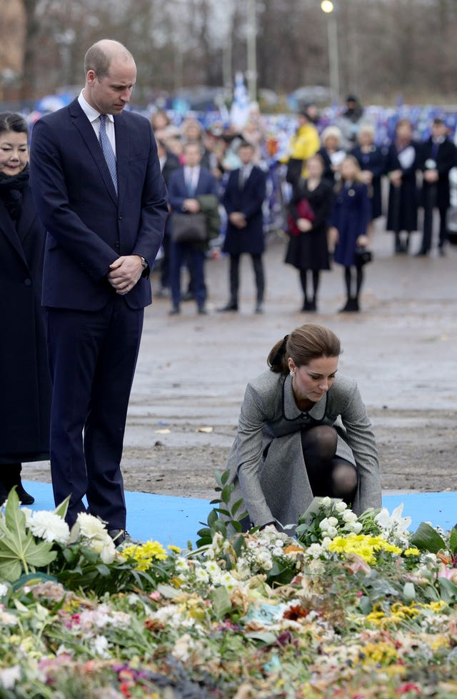 Kate lays flowers at the tribute site