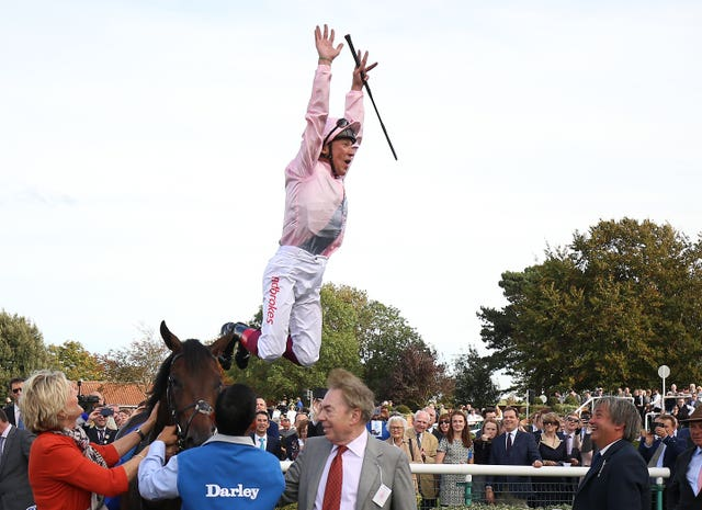 Frankie Dettori leaps from Too Darn Hot after winning the Dewhurst Stakes