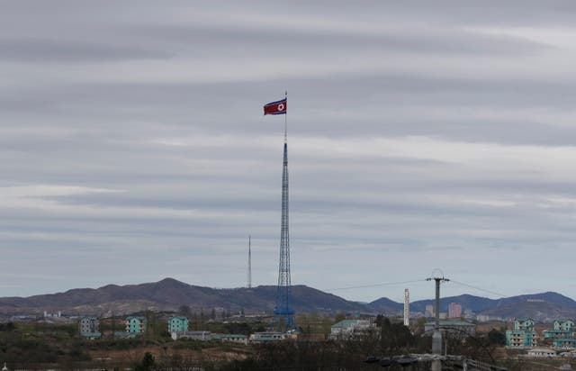 A North Korean flag flutters in the wind (Lee Jin-man/AP)