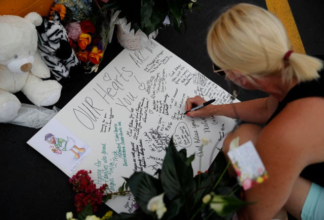 A woman writes a message during a candlelight vigil