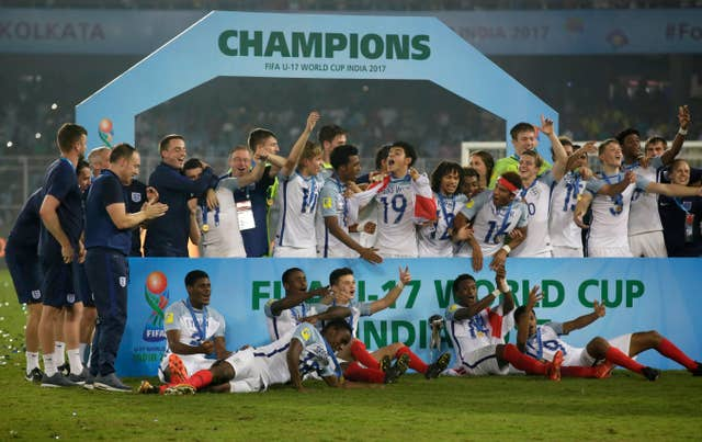 England's team members celebrate during the presentation ceremony after winning the the FIFA U-17 World Cup trophy in India