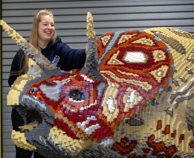 Bright Bricks member of staff Zoe Aris works on one of the brick dinosaurs made out of Lego