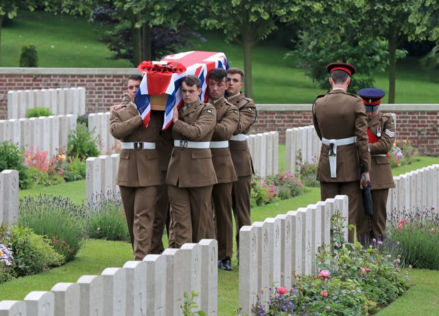 Soldiers carry one of the coffins of two young privates and an unknown soldier, who fought during the First World War, during a burial service at Hermies Hill British Cemetery, near Albert, France