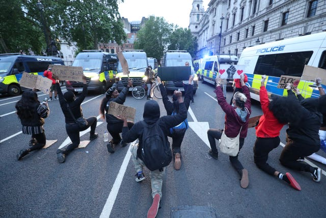 Protestants take a knee for police shootings during a Black Lives Matter rally in Parliament Square