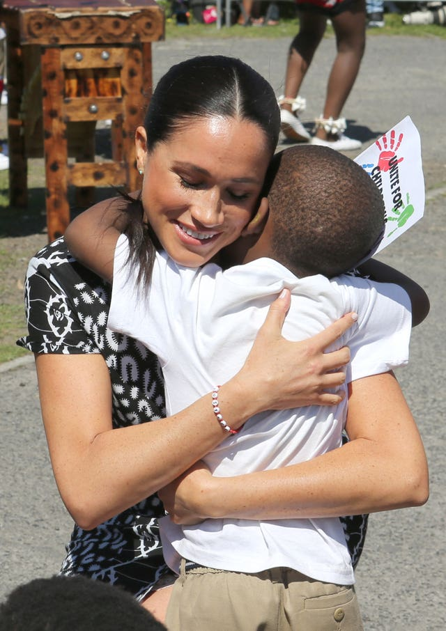 The Duchess of Sussex hugs a young child as she begins her visit to South Africa, with her husband the Duke of Sussex, in the Nyanga Township, Cape Town, during a visit to a workshop that teaches children about their rights, self-awareness and safety and which provides self-defence classes and female empowerment training to young girls in the community
