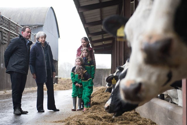 Prime Minister Theresa May is shown around Fairview Farm by owners Stephen and Susanne Jackson and their three daughters Hannah, Abbie and Emily, in Bangor (Stefan Rousseau/PA)