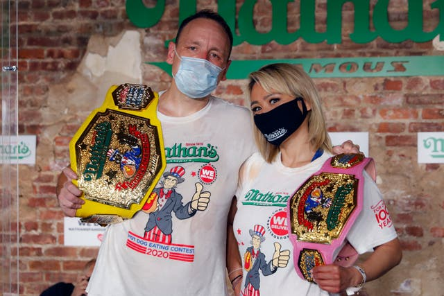 Competitive eaters Joey Chestnut, left, and Miki Sudo, right, pose for a photograph after winning their respective divisions with new world records after the Nathan's Famous July Fourth hot dog eating contest, Saturday, July 4, 2020, in the Brooklyn borough of New York
