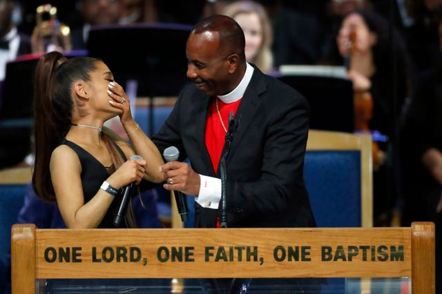 Ariana Grande, left, laughs with Bishop Charles H Ellis