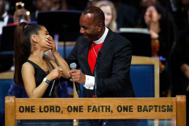 Ariana Grande, left, laughs with Bishop Charles H Ellis