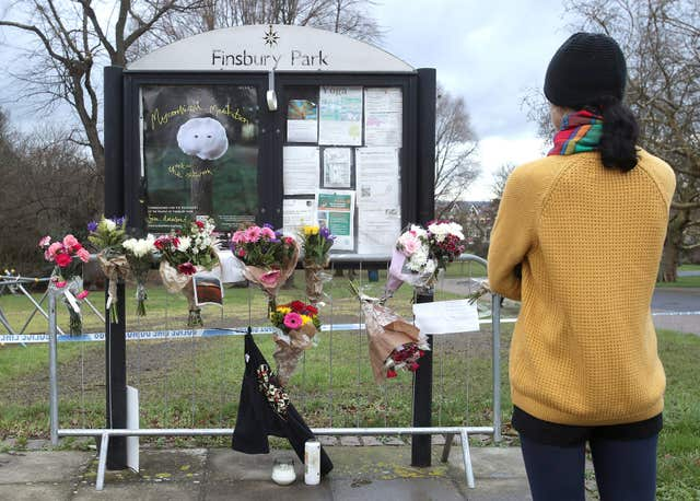 A woman looks at messages and flowers left in tribute to Iuliana Tudos, (Yui Mok/PA)