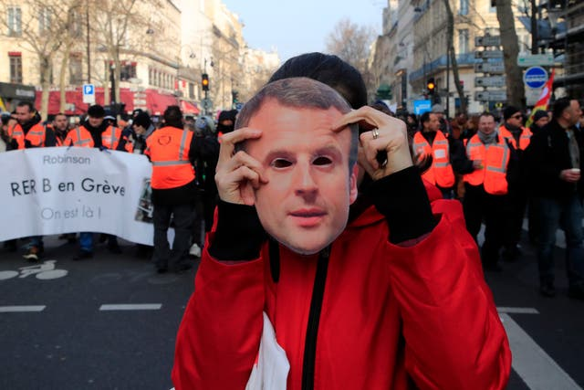 A protester holds a mask of French President Emmanuel Macron during a demonstration in Paris