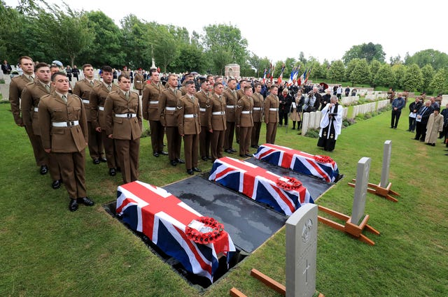 The coffins of two young privates and an unknown soldier, who fought during the first World War, during a burial service at Hermies Hill British Cemetery, near Albert, France