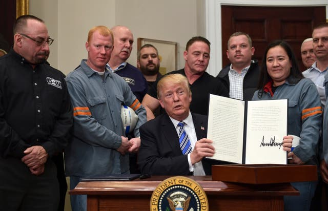 US President Donald Trump holds up his proclamation on steel imports (Susan Walsh/AP)