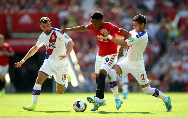 Anthony Martial battles for the ball with two visiting defenders
