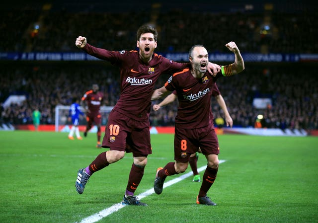 Messi celebrates with Andres Iniesta after putting his side in front at Stamford Bridge (Nick Potts/PA).