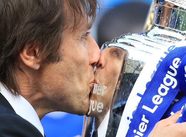 Chelsea head coach Antonio Conte kisses the Premier League trophy after it was presented to the Blues