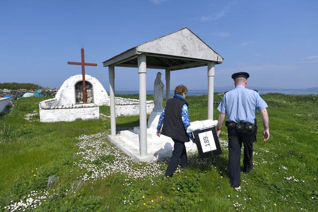 Garda Alan Gallagher and Presiding Officer Carmel McBride carry a polling box used by the few people that live off the coast of Donegal on the island of Inishbofin (Clodagh Kilcoyne/PA)