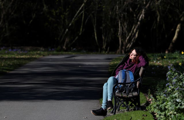 A woman enjoys the sunshine in the Botanic Gardens in Dublin