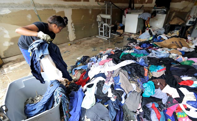 Mother and daughter sort out clothing damaged by floodwaters after Harvey (David J. Phillip/AP)
