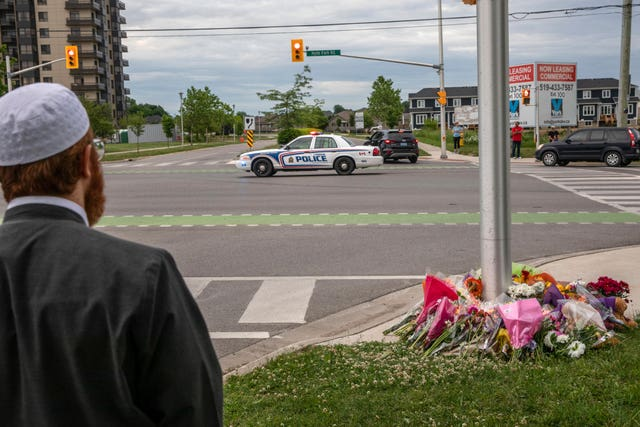 A police car passes the location where a family of five was hit by a driver (Brett Gundlock/AP)