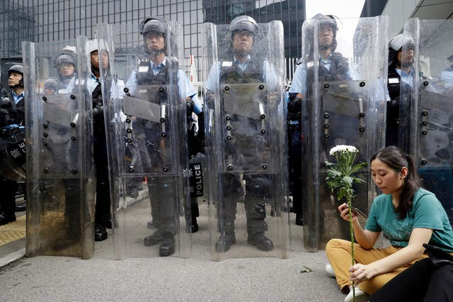 A female protester holds flowers as she sits in front of officers