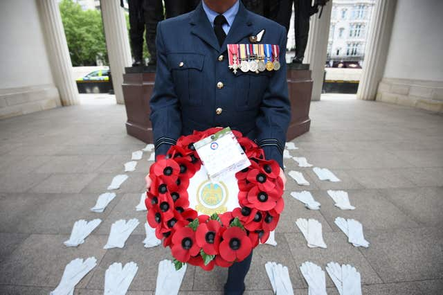 Flight Lieutenant Nigel Painter holds a wreath as he stands among 53 pairs of flying gloves at the Bomber Command Memorial in London's Green Park which represent the men who died in the Dambusters raids (Kirsty O'Connor/PA)