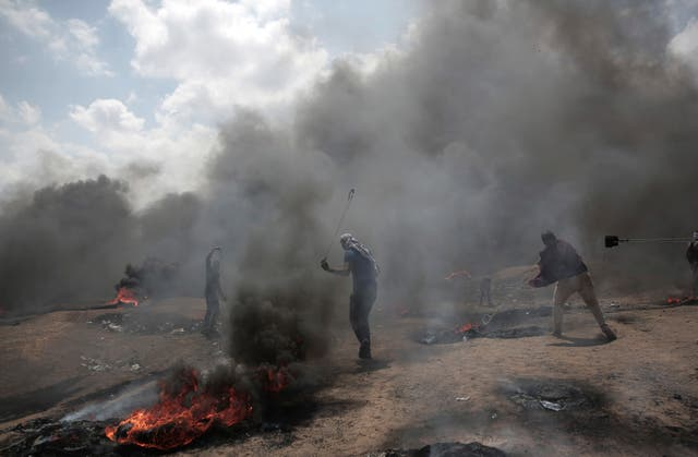 Palestinian protesters hurl stones at Israeli troops during a protest on the border (AP)
