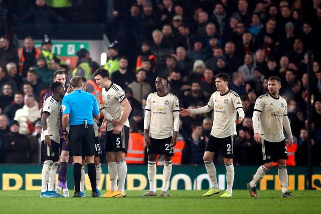 Manchester United players protest to referee Craig Pawson, third left, during their loss to Liverpool