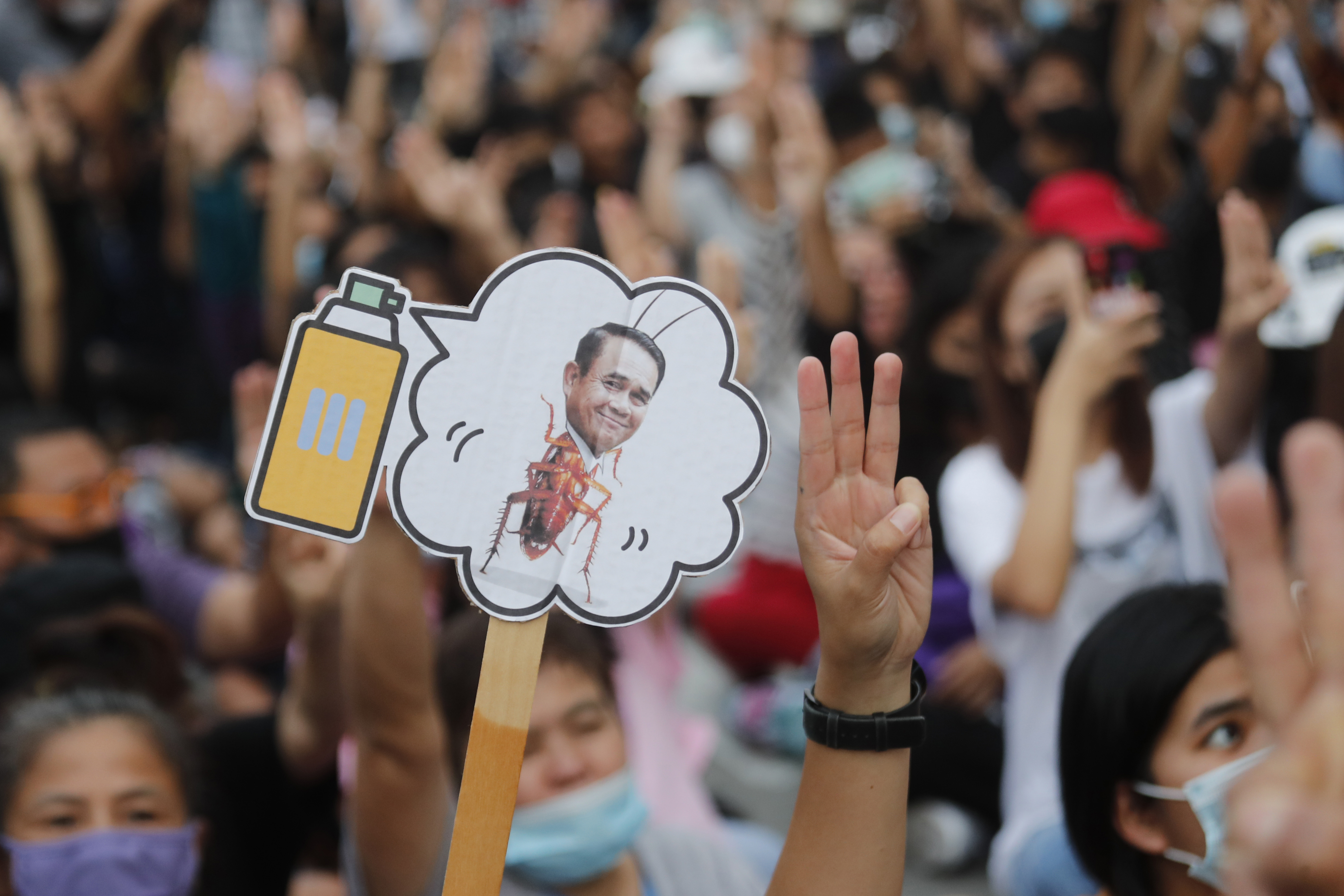 Pro-democracy activists display a placard with Thai prime minister Prayuth Chan-ocha's head attached to a cockroach