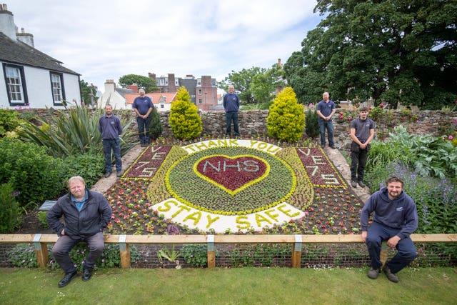 (clockwise from top) Iain Tait, Kyle Storrie, Rory Armatage, Scott Rowan, Johnn Stevens, Dave Brunton and Bruce Collins, from East Lothian Council's Amenity Services stand alongside the floral display they created acknowledging the 75th anniversary of VE Day and thanking the NHS during the current Covid-19 pandemic in the Lodge Grounds at North Berwick