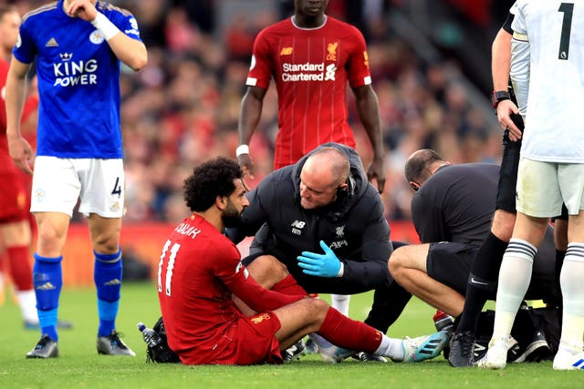 Liverpool's Mohamed Salah sits injured on the pitch