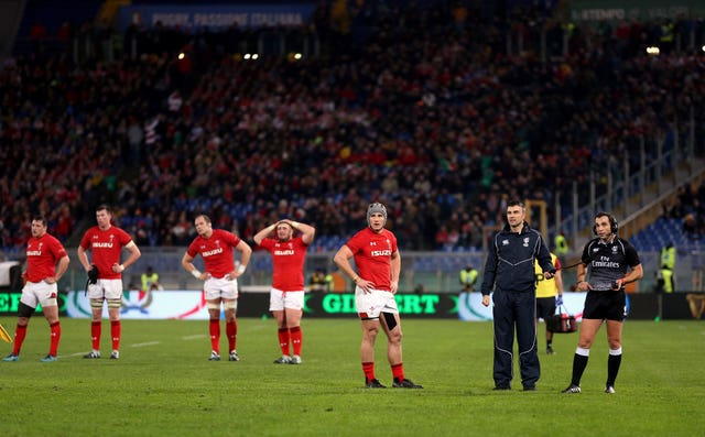 The Wales players wait as the referee Mathieu Raynal (right) watches a replay on the big screen