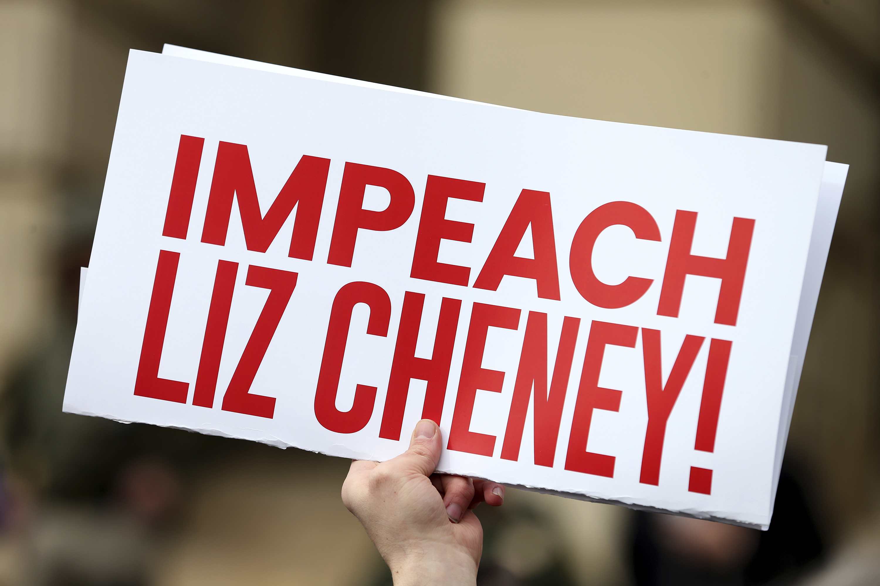 A Donald Trump supporter holds an'Impeach Liz Cheney sign during a protest
