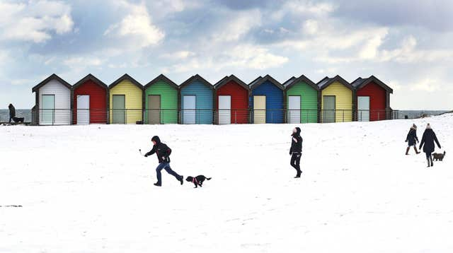 People walk their dogs on Blyth Beach in Northumberland (Owen Humphreys/PA)