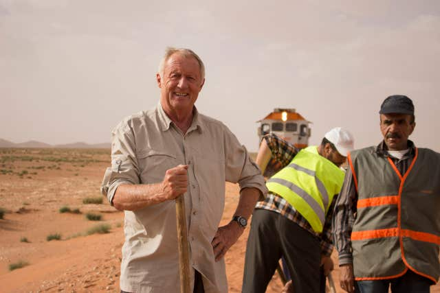 Chris Tarrant helps workers to clear sand off the tracks