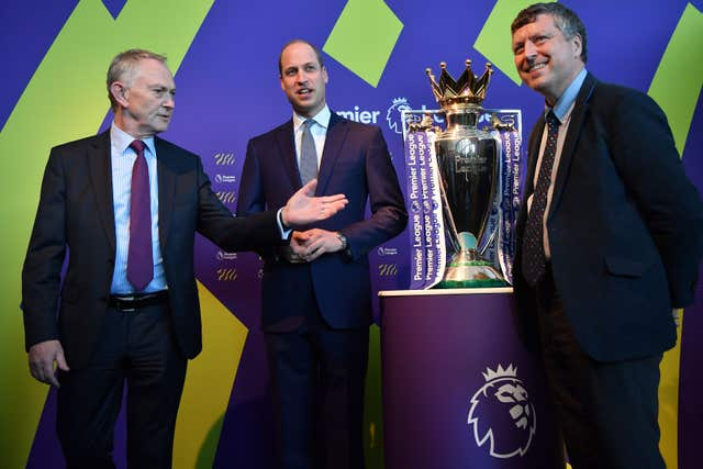 The Duke of Cambridge (centre) standing next to the Premier League football trophy (Ben Stansall/PA)