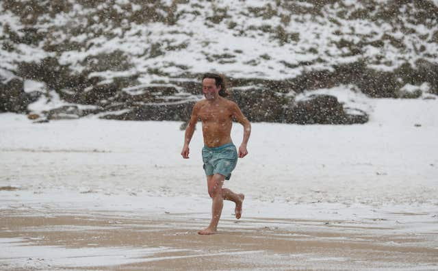 A swimmer braves the snowy conditions at King Edwards bay near Tynemouth (Owen Humphreys/PA)