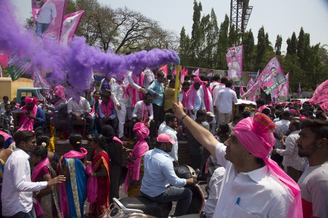 A supporter of Telangana Rashtra Samithi, a regional political party, sprays colour as he participates with others in an election campaign rally in Hyderabad