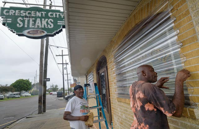 Storm protectors are screwed in at a restaurant in New Orleans ahead of Storm, Barry's arrival