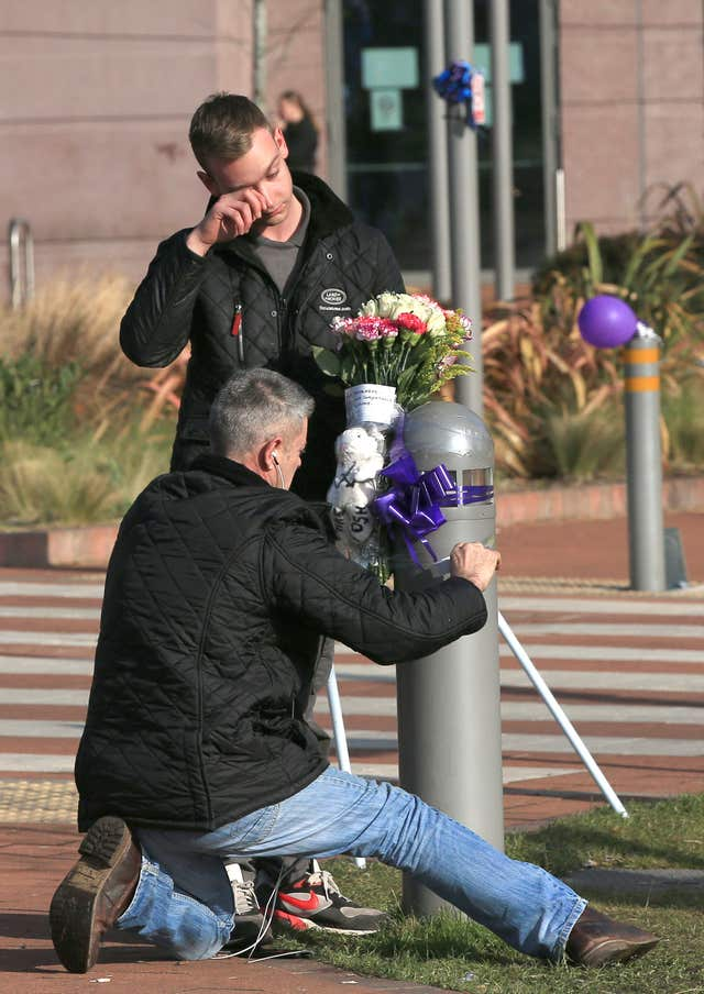 Mourners ties flowers to a post outside the hospital following news of the boy's death (Peter Byrne/PA)