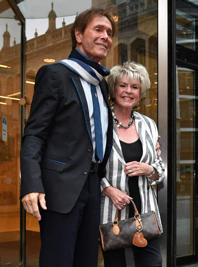 Sir Cliff Richard leaves the building with Gloria Hunniford, where the case is being heard (Dominic Lipinski/PA)