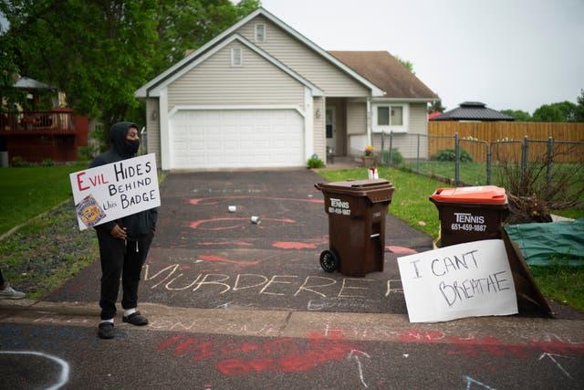 Amanuel Soquar stands outside Minneapolis police officer Derek Chauvin's house