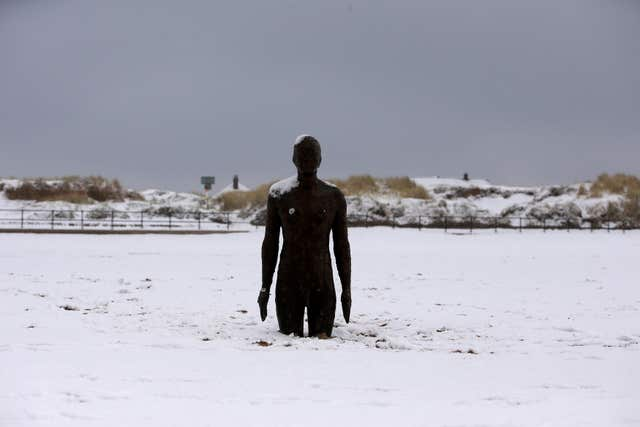 Another Place by Anthony Gormley surrounded by snow on Crosby Beach near Liverpool (Peter Byrne/PA)