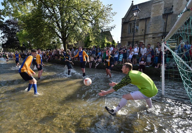 Bourton Rovers 1st team (yellow sleeves) and Bourton Rovers 2nd team (in solid blue) play each other in the annual traditional river football match in the Cotswolds village of Bourton-in-the-Water
