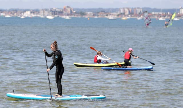 Paddle boarders enjoy the warm weather in Poole Harbour in Dorset