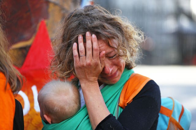 A mother cries while she holds her baby during a protest organised by Mothers Rise Up at Downing Street