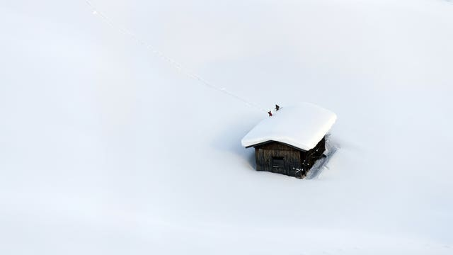 People clear a roof from snow in Lofer, Austrian province of Salzburg