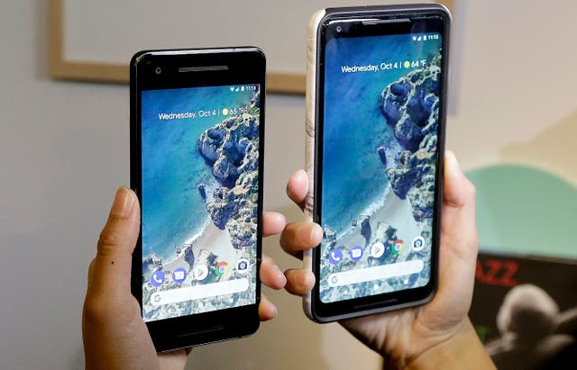 A woman holds up the Google Pixel 2 and Pixel 2 XL phones