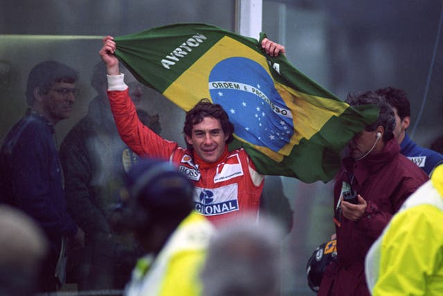 Senna flying the Brazilian flag as he works his way through the crowd to the winner's podium after victory in the European Grand Prix at Donington Park