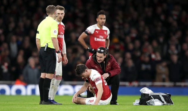 Laurent Koscielny (floor) was injured in the FA Cup defeat to Manchester United